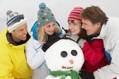 Groupe d'amis construisant le bonhomme de neige des vacances de ski Photos libres de droits