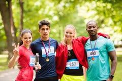 Groupe d'amis convenables de jeunes heureux après avoir fini la course Photo libre de droits