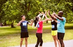 Groupe d'amis convenables de jeunes heureux après avoir fini la course Image libre de droits
