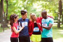 Groupe d'amis convenables de jeunes heureux après avoir fini la course Images stock