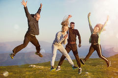 Groupe d'amis courant heureusement ensemble dans l'herbe et sauter photo stock