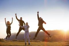 Groupe d'amis courant heureusement ensemble dans l'herbe et sauter Image libre de droits