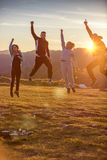 Groupe d'amis courant heureusement ensemble dans l'herbe et sauter Image stock
