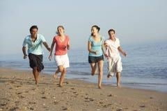 Groupe d'amis courant le long de la plage Photos stock