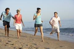 Groupe d'amis courant le long de la plage Images libres de droits