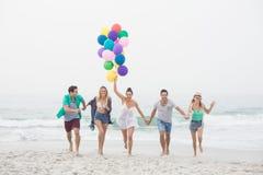 Groupe d'amis courant sur la plage avec des ballons Photographie stock
