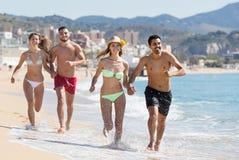 Groupe d'amis courant sur le sable à la plage Image stock