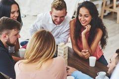 Groupe d'amis créatifs s'asseyant à la table en bois Les gens ayant l'amusement tout en jouant le jeu de société Image stock