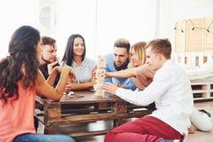 Groupe d'amis créatifs s'asseyant à la table en bois Les gens ayant l'amusement tout en jouant le jeu de société Photos stock