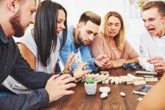 Groupe d'amis créatifs s'asseyant à la table en bois Les gens ayant l'amusement tout en jouant le jeu de société Photo stock