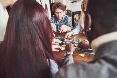 Groupe d'amis créatifs s'asseyant à la table en bois Les gens ayant l'amusement tout en jouant le jeu de société Photographie stock libre de droits