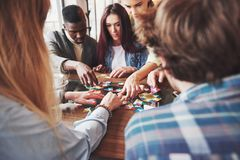 Groupe d'amis créatifs s'asseyant à la table en bois Les gens ayant l'amusement tout en jouant le jeu de société Images libres de droits