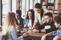 Groupe d'amis créatifs s'asseyant à la table en bois Les gens ayant l'amusement tout en jouant le jeu de société Image libre de droits
