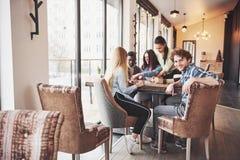 Groupe d'amis créatifs s'asseyant à la table en bois Les gens ayant l'amusement tout en jouant le jeu de société Photos libres de droits