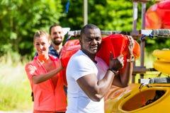 Groupe d'amis déchargeant le kayak de la remorque de bateau Photographie stock