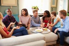 Groupe d'amis détendant à la maison sur Sofa Together Photos stock