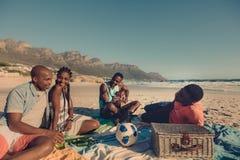 Groupe d'amis détendant à la plage Photo libre de droits