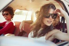Groupe d'amis détendant dans la voiture pendant le voyage par la route Photos libres de droits