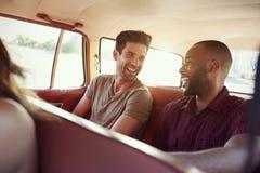 Groupe d'amis détendant dans la voiture pendant le voyage par la route Photo libre de droits