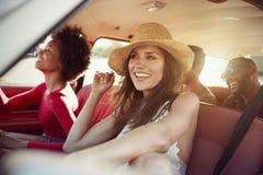 Groupe d'amis détendant dans la voiture pendant le voyage par la route Image libre de droits