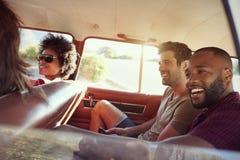 Groupe d'amis détendant dans la voiture pendant le voyage par la route Images libres de droits