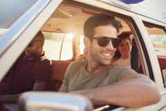 Groupe d'amis détendant dans la voiture pendant le voyage par la route Photographie stock libre de droits