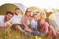 Groupe d'amis détendant en dehors des tentes des vacances de camping Image libre de droits