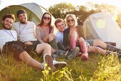 Groupe d'amis détendant en dehors des tentes des vacances de camping Photo stock