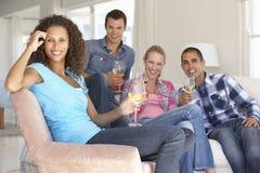 Groupe d'amis détendant sur Sofa Drinking Wine At Home ensemble Image libre de droits