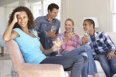Groupe d'amis détendant sur Sofa Drinking Wine At Home ensemble Image stock