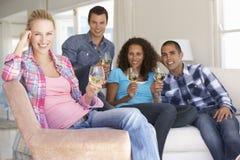 Groupe d'amis détendant sur Sofa Drinking Wine At Home ensemble Photo stock