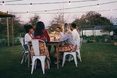 Groupe d'amis dînant dans le restaurant de jardin Photographie stock libre de droits