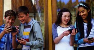 Groupe d'amis d'école à l'aide du téléphone portable en dehors de l'école banque de vidéos