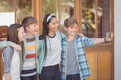 Groupe d'amis d'école prenant le selfie avec le téléphone portable Photos stock