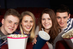 Groupe d'amis d'adolescent observant le film dans le cinéma Images stock