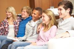 Groupe d'amis d'adolescent s'asseyant sur le sofa à la maison Images libres de droits