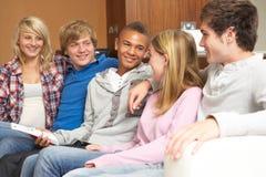 Groupe d'amis d'adolescent s'asseyant sur le sofa à la maison Photos libres de droits