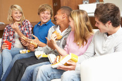 Groupe d'amis d'adolescent s'asseyant sur le sofa à la maison Photographie stock