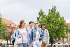 Groupe d'amis d'université marchant dehors Photo libre de droits