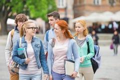 Groupe d'amis d'université marchant dehors Photos libres de droits