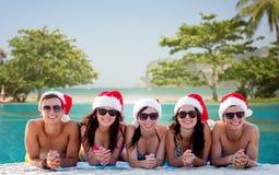 Groupe d'amis dans des chapeaux d'aide de Santa sur la plage Photo libre de droits