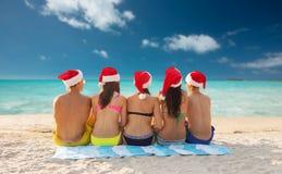 Groupe d'amis dans des chapeaux d'aide de Santa sur la plage Photographie stock libre de droits