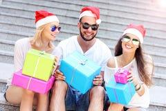 Groupe d'amis dans des chapeaux de Santa avec des présents Photo libre de droits
