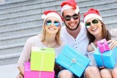Groupe d'amis dans des chapeaux de Santa avec des présents Photographie stock libre de droits