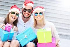 Groupe d'amis dans des chapeaux de Santa avec des présents Photo stock