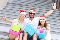Groupe d'amis dans des chapeaux de Santa avec des présents Photographie stock