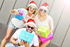 Groupe d'amis dans des chapeaux de Santa avec des présents Photos stock