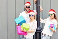 Groupe d'amis dans des chapeaux de Santa avec des présents Photos libres de droits
