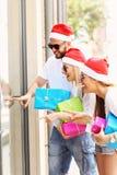 Groupe d'amis dans des chapeaux de Santa avec des présents Images stock