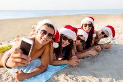 Groupe d'amis dans des chapeaux de Santa avec le smartphone Photo libre de droits
